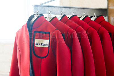 Buy stock photo Shot of wetsuits on a hanger