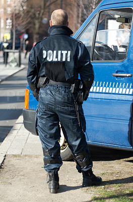 Buy stock photo A policeman standing next to his van outside - rear view