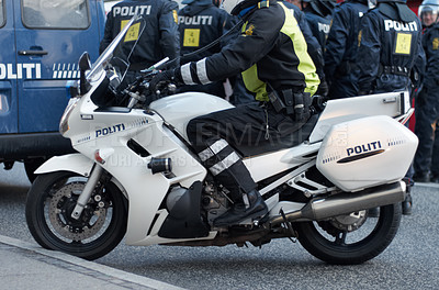 Buy stock photo A police man  riding on his motorcycle down the road