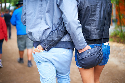 Buy stock photo A young couple walking outside with their hands on each other's buttocks