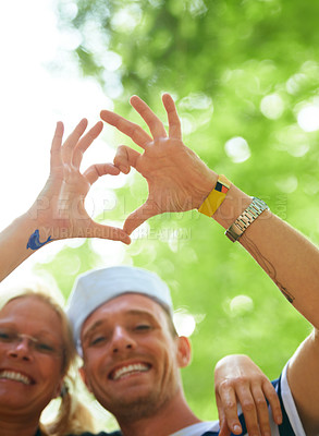 Buy stock photo Shot of two people making a heart-shape with their hands at a music festival