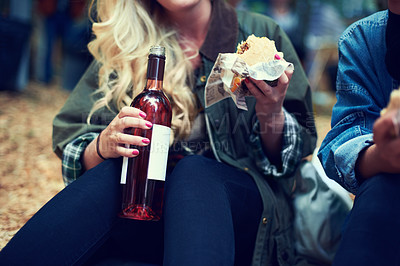 Buy stock photo Cropped shot of two women drinking and having a snack at an outdoor festival
