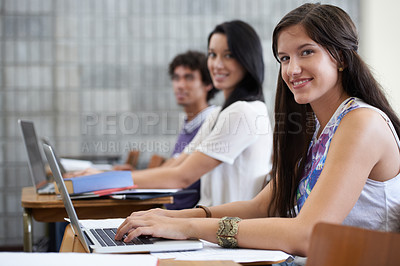 Buy stock photo Shot of a happy young college student working at a laptop in class