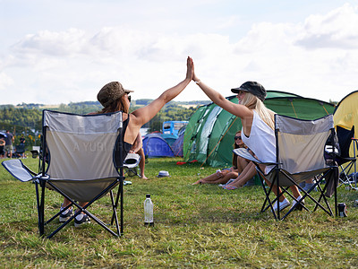 Buy stock photo Rearview shot of two friends giving each other a high five at an outdoor festival