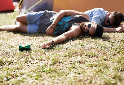 Buy stock photo Shot of two young men lying on the grass after drinking too much at an outdoor festival