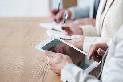 Buy stock photo Cropped shot of a businessman using a digital tablet during a meeting
