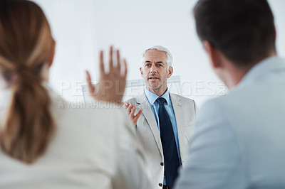 Buy stock photo Rearview shot of a mature business man taking questions at a work seminar