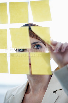Buy stock photo Shot of a businesswoman arranging sticky notes on a glass wal