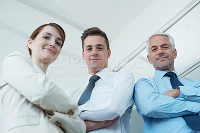 Buy stock photo Portrait of a group of smiling business people with their arms crossed