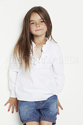 Buy stock photo Studio portrait of a cute little girl leaning against a white wall