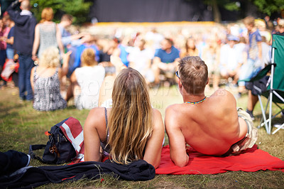 Buy stock photo A young couple lying on the grass at an outdoor event