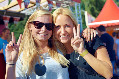 Buy stock photo Shot of two women showing the peace sign at a festival