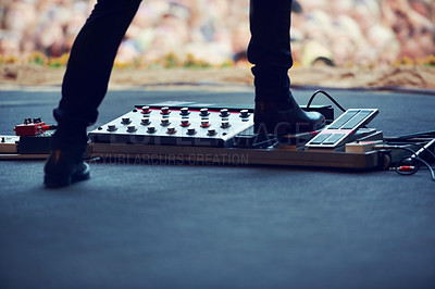Buy stock photo Cropped image of a performer pushing down on a distortion pedal on stage