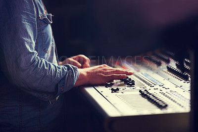 Buy stock photo Cropped shot of a sound engineer sliding faders on a mixing desk