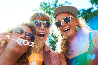 Buy stock photo Shot of a group of young women having fun blowing bubbles