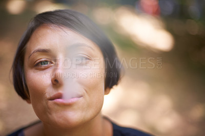Buy stock photo Portrait of a woman blowing smoke out of her mouth