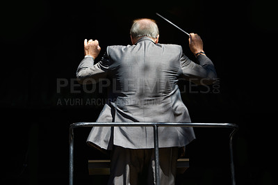 Buy stock photo Cropped rear view of an orchestra conductor waving his baton