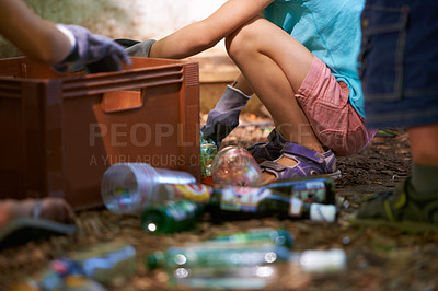 Buy stock photo Cropped view of two women picking up empty bottles of alcohol after a festival