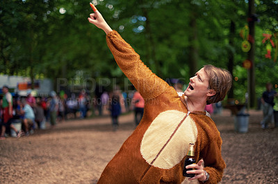 Buy stock photo Shot of a young man drinking outside while dressed in an animal costume