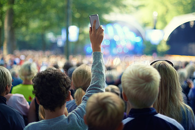 Buy stock photo Shot of a member of the crowd taking a picture with his camera phone at a music festival