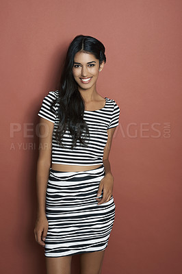 Buy stock photo Studio shot of a beautiful young Indian woman standing against a brown background in casual attire