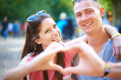 Buy stock photo A young couple making a heart sign with their hands