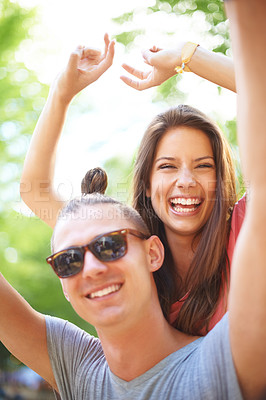 Buy stock photo A trendy young man giving his female friend a piggyback ride
