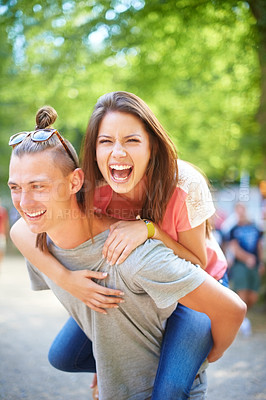 Buy stock photo A trendy young man giving his girlfriend a piggyback ride