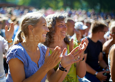 Buy stock photo Two mature woman sitting outdoors at a music festival