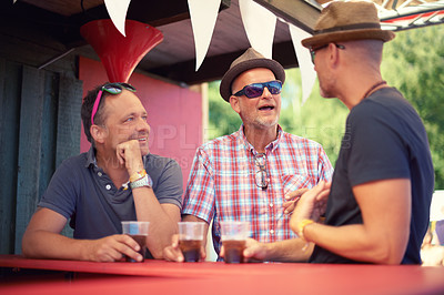 Buy stock photo Cropped shot of three male friends talking and having a drink at a festival