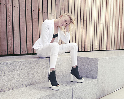 Buy stock photo Shot of a trendy young woman sitting outside on the steps