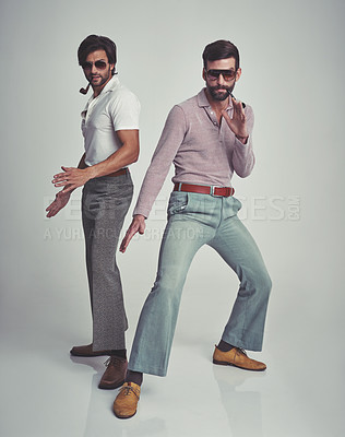 Buy stock photo Studio shot of two men standing together while wearing retro 70s wear and striking a pose