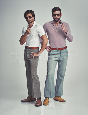 Buy stock photo Studio shot of two men standing together while wearing retro 70s wear and smoking pipes