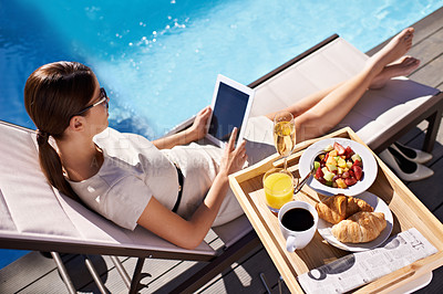 Buy stock photo An attractive young woman enjoying her breakfast poolside