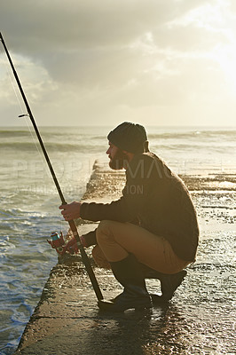 Buy stock photo A young man fishing on the pier