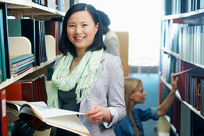 Buy stock photo A young woman holding a book in the library