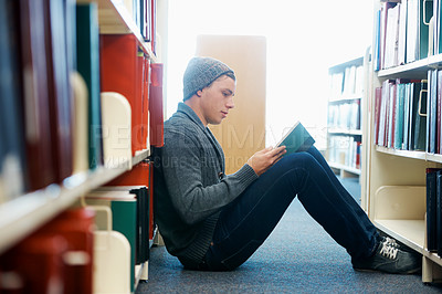 Buy stock photo A young man sitting on the floor and reading in a library