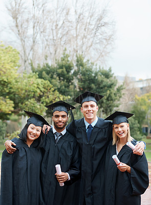 Buy stock photo A group of college graduates standing in cap and gown and holding their diplomas