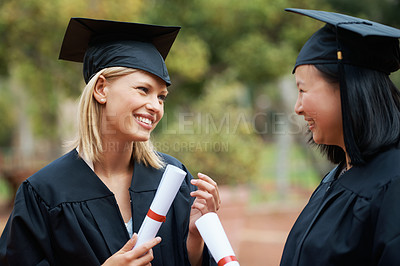 Buy stock photo Two young college graduates holding their diplomas while wearing cap and gown