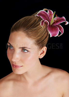 Buy stock photo An attractive young woman with a flower in her hair against a black background
