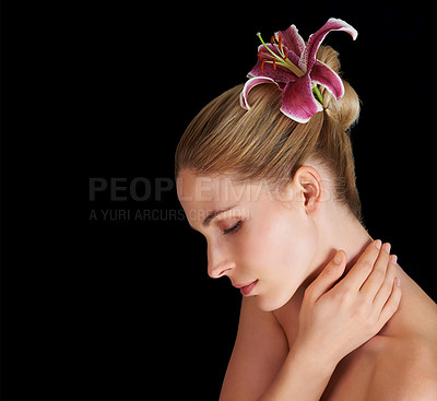 Buy stock photo A beautiful young woman with a flower in her hair isolated on black