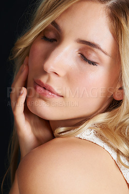 Buy stock photo A beautiful young blonde woman with her eyes closed hand her hand on her face