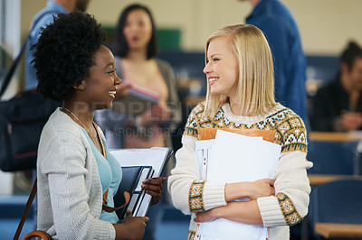 Buy stock photo Shot of two university students talking together in a lecture hall