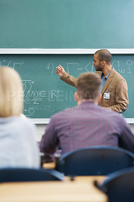 Buy stock photo Shot of a college professor giving a lesson to his students in the lecture hall