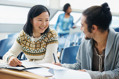 Buy stock photo Shot of a two university students talking to each other in a lecture hall