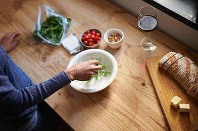 Buy stock photo A young woman making a salad in her kitchen