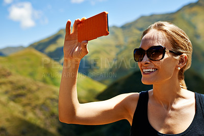 Buy stock photo A young woman taking a picture in the mountainside