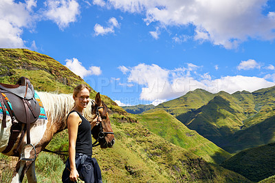 Buy stock photo A young woman with her horse on a mountain trek