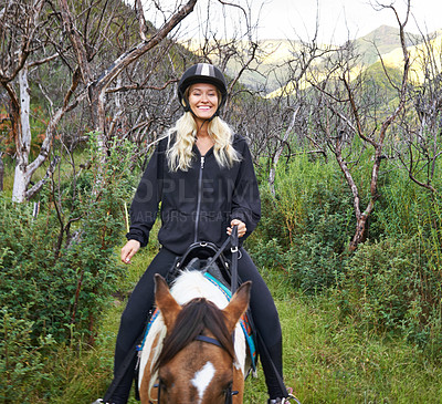 Buy stock photo An attractive young woman riding a horse along a mountain trail