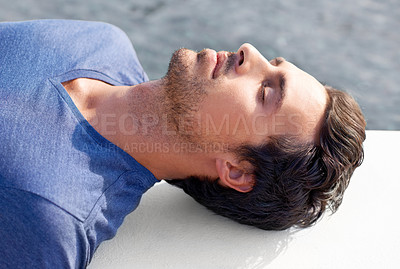 Buy stock photo Cropped shot of a handsome man lying down with his eyes closed